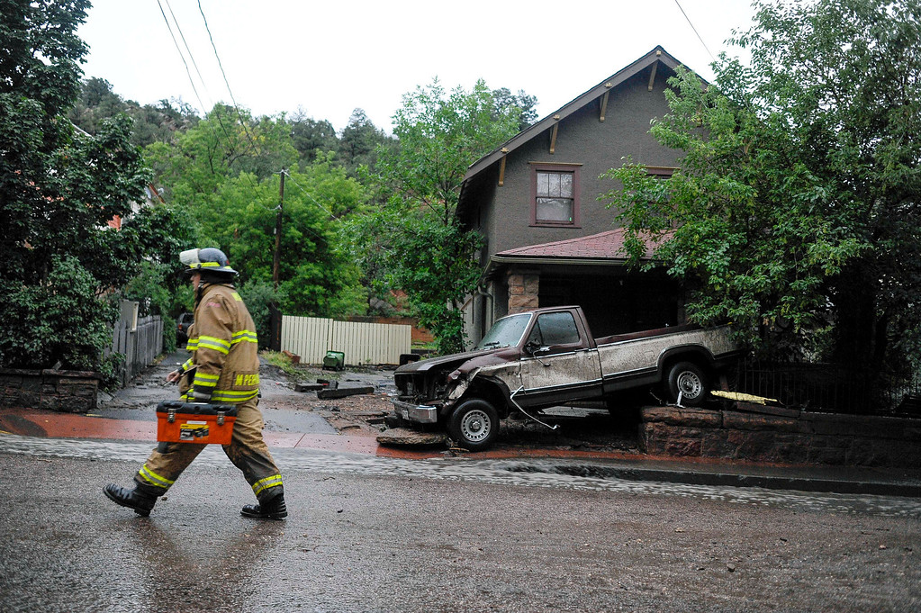 . A firefighter walks up Canon Avenue  after another flash flood hit the area, Friday, Aug. 9, 2013 in Manitou, Colo. A mudslide has closed U.S. 24 between Cascade and Manitou Springs, and flash flooding in Manitou Springs is stranding vehicles in high, fast-moving water. (AP Photo/The Colorado Springs Gazette, Michael Ciaglo)