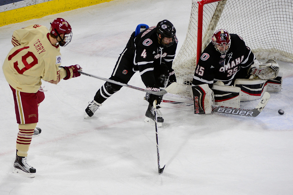 . Denver Pioneers forward Troy Terry (19) tries to sneak a shot around Nebraska-Omaha Mavericks goalie Evan Weninger (35) during the first period at Magness Arena on March 4, 2016 in Denver, Colorado. (Photo by Brent Lewis/The Denver Post)