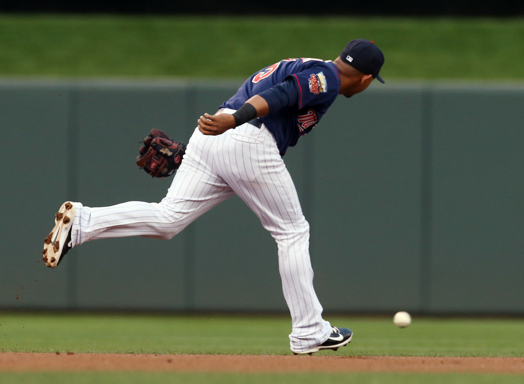 . A single off the bat of Detroit Tigers designated hitter Victor Martinez goes wide of Minnesota Twins shortstop Eduardo Escobar in the first inning of a baseball game, Friday, Aug. 22, 2014, in Minneapolis. (AP Photo/Jim Mone)