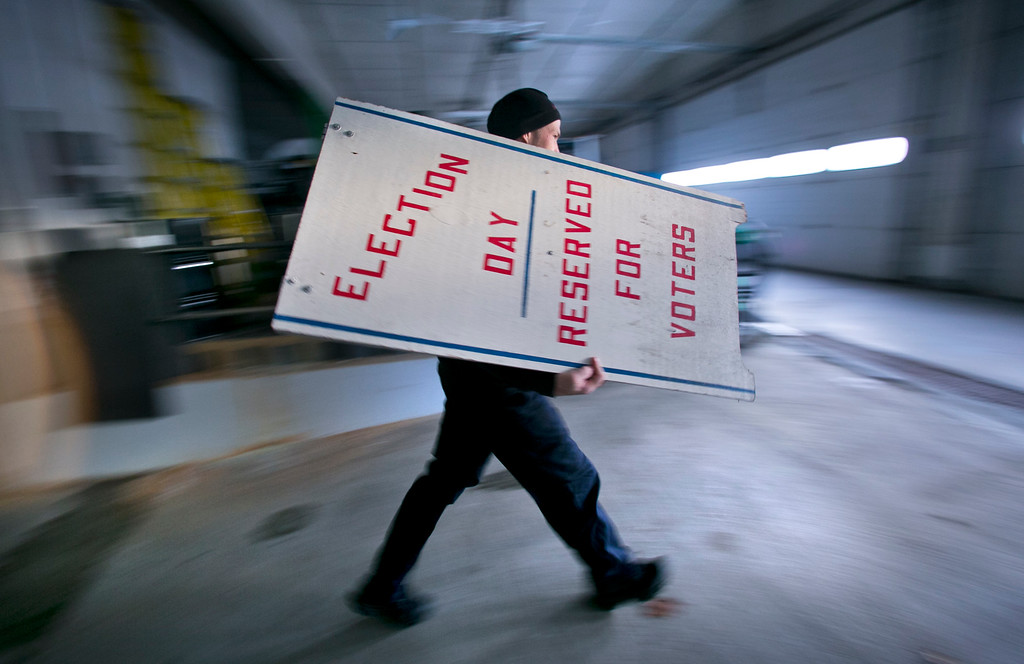 . Firefighter Cheyne Hansen takes a sign out of storage at a municipal garage while helping election officials scramble to set up a last-minute polling place, Tuesday, Nov. 4, 2014, in Camden, Maine.  Sunday\'s snow storm knocked out power to much of the town, including the usual voting location at the public safety building, so officials decided to set up a polling place at a nearby church hall. (AP Photo/Robert F. Bukaty)