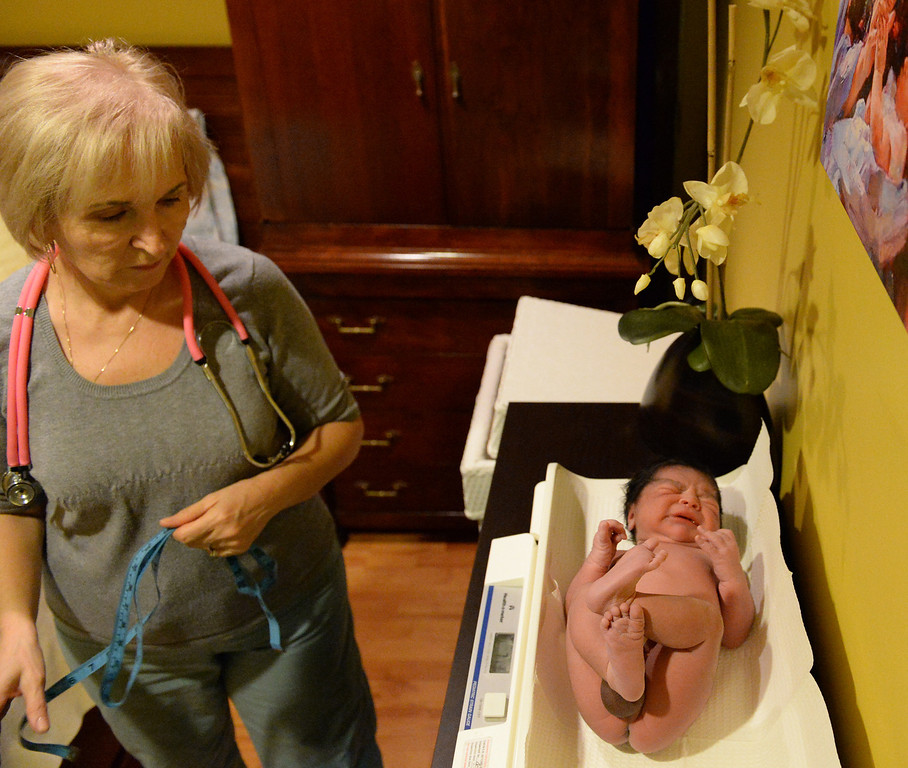 . Midwife Simona Istrate weighs Nicholas shortly after being born by water birth at the Natural Birth Center and Women\'s Wellness in Whittier on December 29, 2013. Birthing centers and home births are becoming more popular and the Birth Center in Whittier is doing so well it opened a second office in Beverly Hills. (Staff Photo by Keith Durflinger/Whittier Daily News)