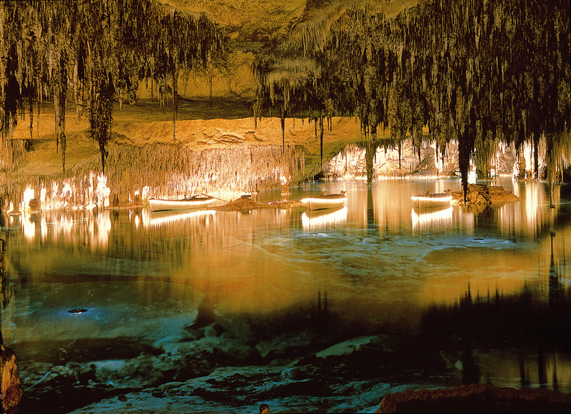 interior of cave with stalactites and boats in the water