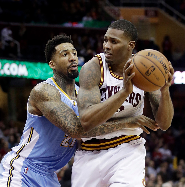 . Cleveland Cavaliers\' Alonzo Gee, right, tries to get past Denver Nuggets\' Wilson Chandler, left, during the second quarter of an NBA basketball game on Wednesday, Dec. 4, 2013, in Cleveland. (AP Photo/Tony Dejak)