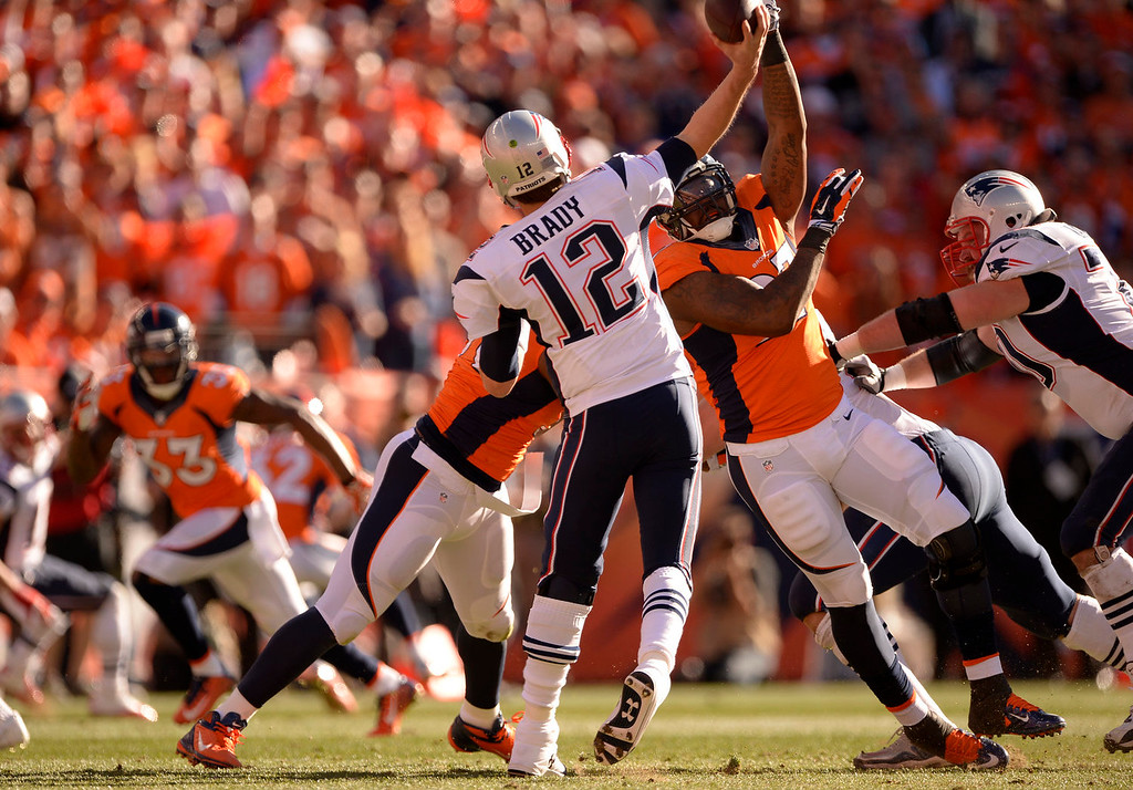 . Denver Broncos defensive end Malik Jackson (97) puts pressure on New England Patriots quarterback Tom Brady (12) during the first quarter. The Denver Broncos vs. The New England Patriots in an AFC Championship game  at Sports Authority Field at Mile High in Denver on January 19, 2014. (Photo by John Leyba/The Denver Post)