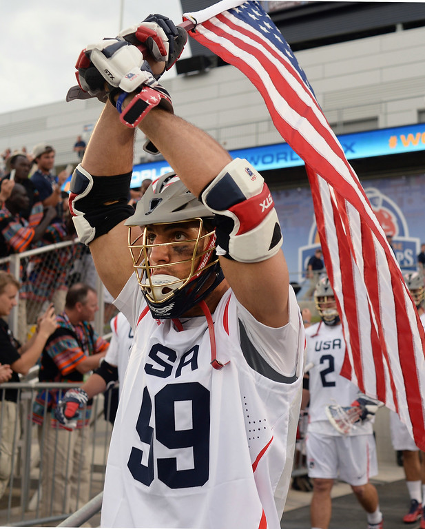 . American midfielder Paul Rabil carried the flag onto the field Thursday night. The United States took on Canada in the opening game of the FIL World Lacrosse Championships Thursday night, July 10, 2014.   Photo by Karl Gehring/The Denver Post