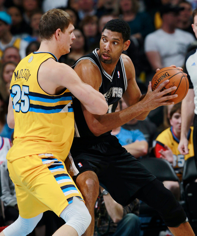. San Antonio Spurs center Tim Duncan, right, works ball inside as Denver Nuggets center Timofey Mozgov, of Russia, covers in the first quarter of an NBA basketball game in Denver, Friday, March 28, 2014. (AP Photo/David Zalubowski)