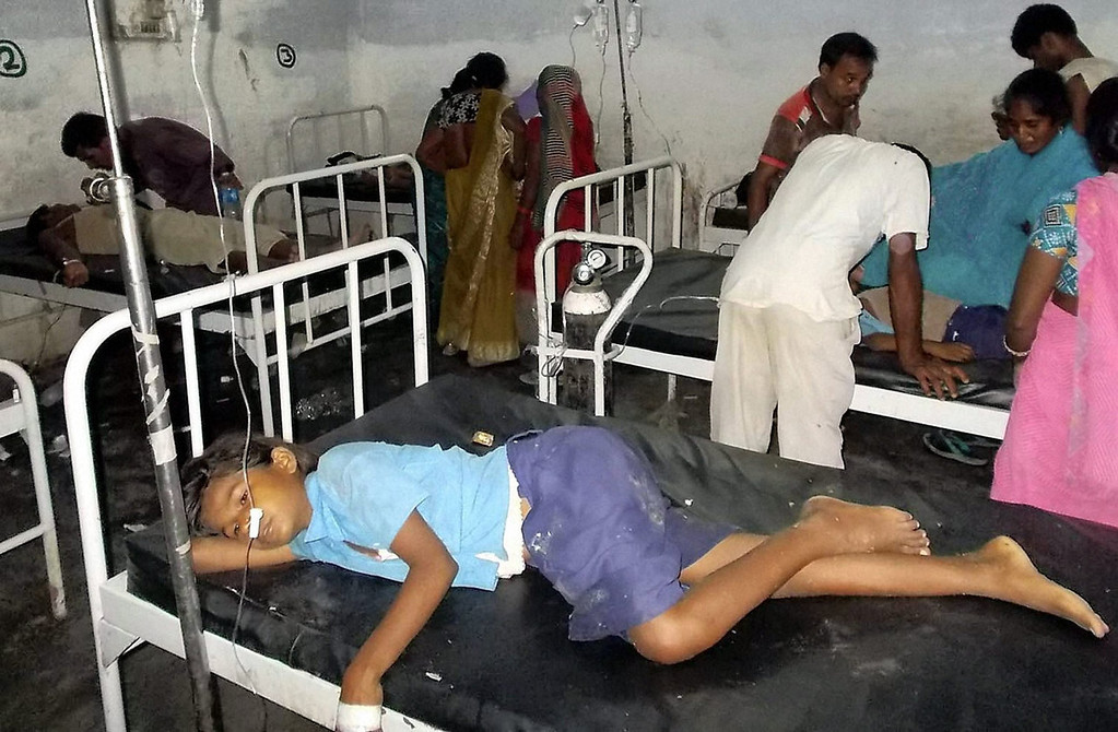 . Schoolchildren receive treatment at a hospital after falling ill soon after eating a free meal at a primary school in Chhapra district on Tuesday, July 16, 2013, in the eastern Indian state of Bihar. At least 20 children have died and more are sick after eating free meals in the school, an official said Wednesday.  The children are age 8 to 11.  (AP Photo)