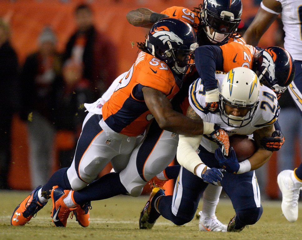 . Denver Broncos outside linebacker Danny Trevathan (59), strong safety Mike Adams (20) and cornerback Omar Bolden (31) tackle San Diego Chargers running back Ryan Mathews (24) during the first quarter. The Denver Broncos vs. the San Diego Chargers at Sports Authority Field at Mile High in Denver on December 12, 2013. (Photo by John Leyba/The Denver Post)