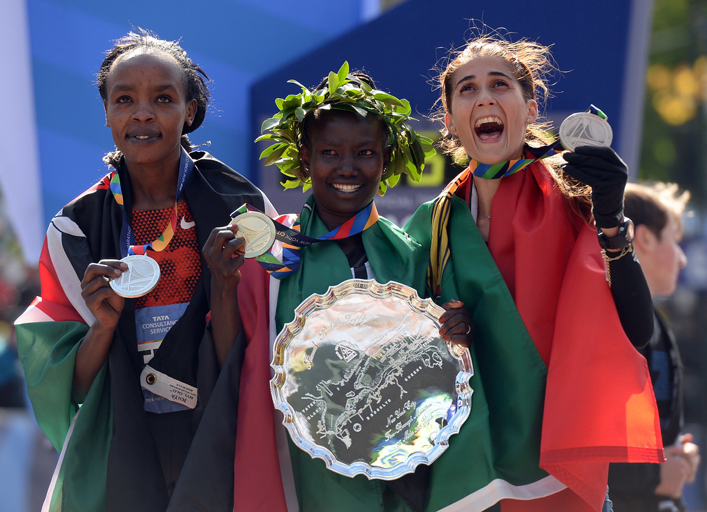 . First place finisher Mary Keitany(C) of Kenya, poses with Jemima Sumgong (L, second) of Kenya and Sara Moreira (R, third) of Portugal following Women\'s 2014 TCS New York City Marathon November 2, 2014 in New York. AFP PHOTO/Don EmmertDON EMMERT/AFP/Getty Images