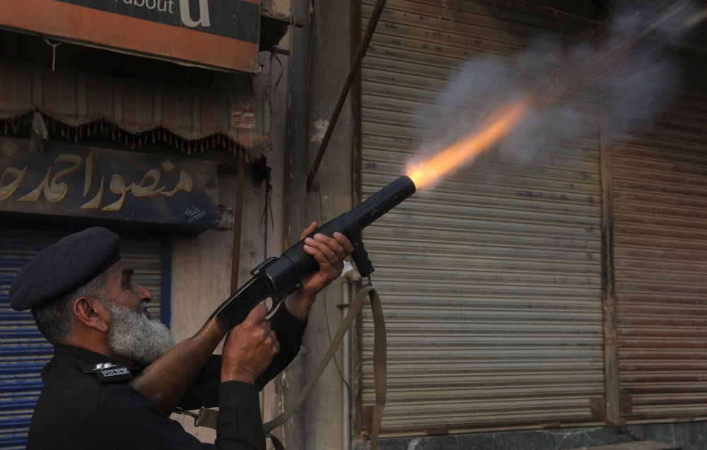 . A Pakistani policeman fires tear gas towards Christian demonstrators during a protest against the attack on the homes of members of the Christian community by Muslim demonstrators in Lahore on March 10, 2013. Christians demonstrated around Pakistan on March 10 after a Muslim mob torched more than 100 Christian homes following allegations of blasphemy. More than 3,000 Muslims rampaged through Joseph Colony, a Christian area of the eastern city of Lahore, on March 9 after allegations that a Christian had made derogatory remarks about the Prophet Mohammed three days earlier. Arif Ali/AFP/Getty Images