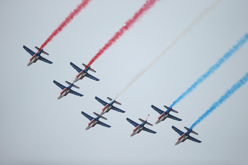 . French planes trailing red, white and blue pass over the main international ceremony commemorating the 70th anniversary of the D-Day invasion with 17 heads of state at Sword Beach on June 6, 2014 at Ouistreham, France.  (Photo by Sean Gallup/Getty Images)