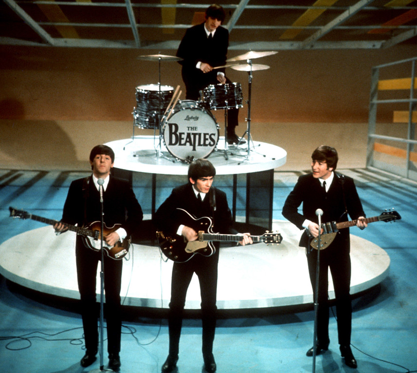". The Beatles perform on the CBS ""Ed Sullivan Show"" in New York Feb. 9, 1964. From left, front, are Paul McCartney, George Harrison and John Lennon. Ringo Starr plays drums. (AP Photo)"