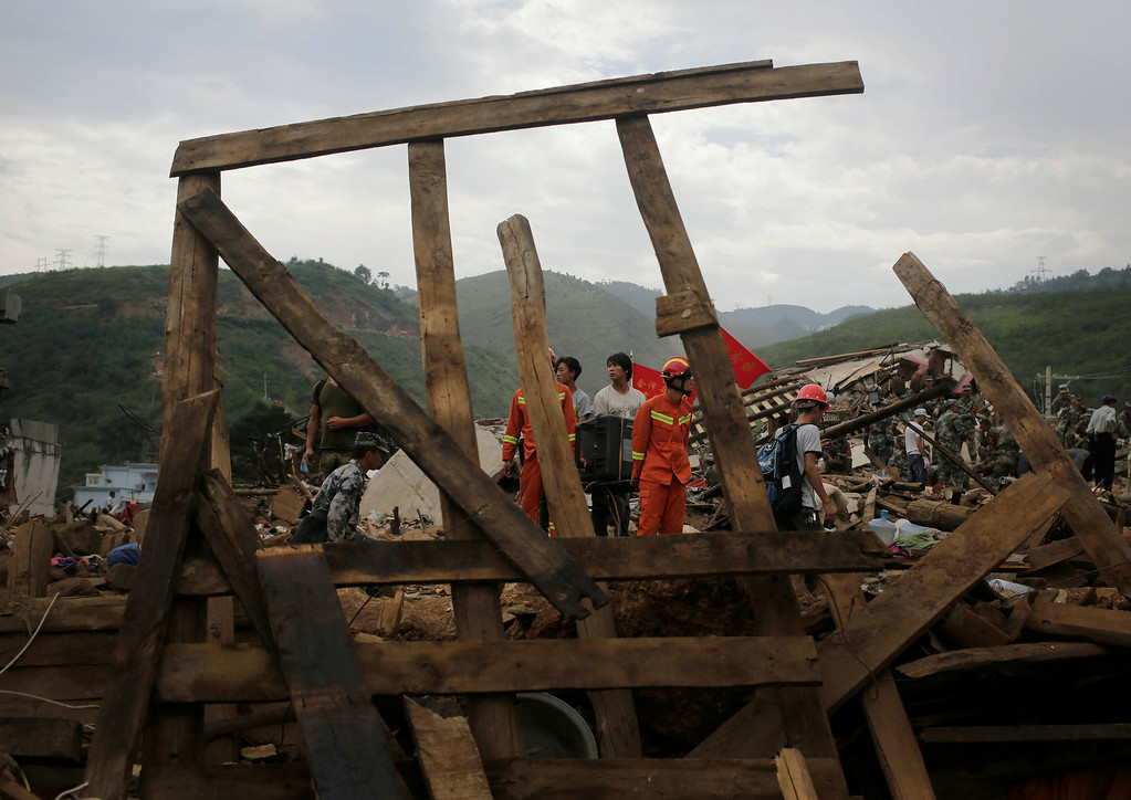 . Rescuers help a villager to carry aTV set out of their destroyed house following a massive earthquake in the town of Longtoushan in Ludian County in southwest China\'s Yunnan Province Tuesday, Aug. 5, 2014. (AP Photo/Andy Wong)