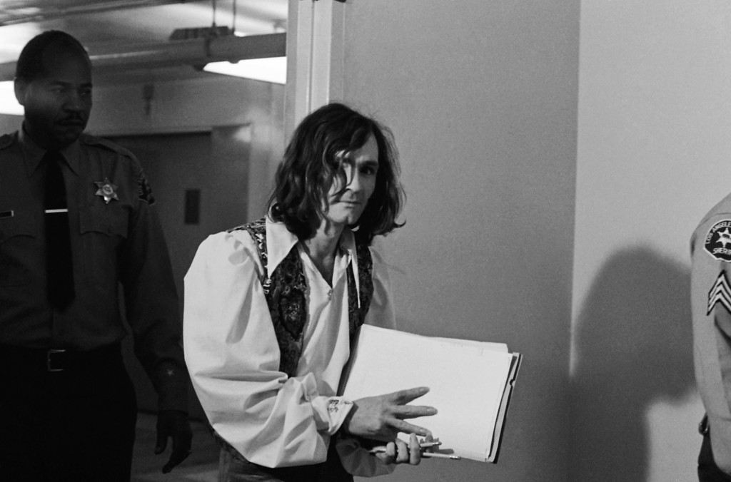 . Charles M. Manson, the hippie-style cult leader charged with the killings of actress Sharon Tate and six others, leaves a Los Angeles courtroom with his pencils and paper after the judge ordered a plea of innocent, Jan. 29, 1970.  Manson, acting as his own lawyer, responded with questions of his own each time the judge asked for a plea. It was his first court appearance since shaving his beard and mustache. (AP Photo)