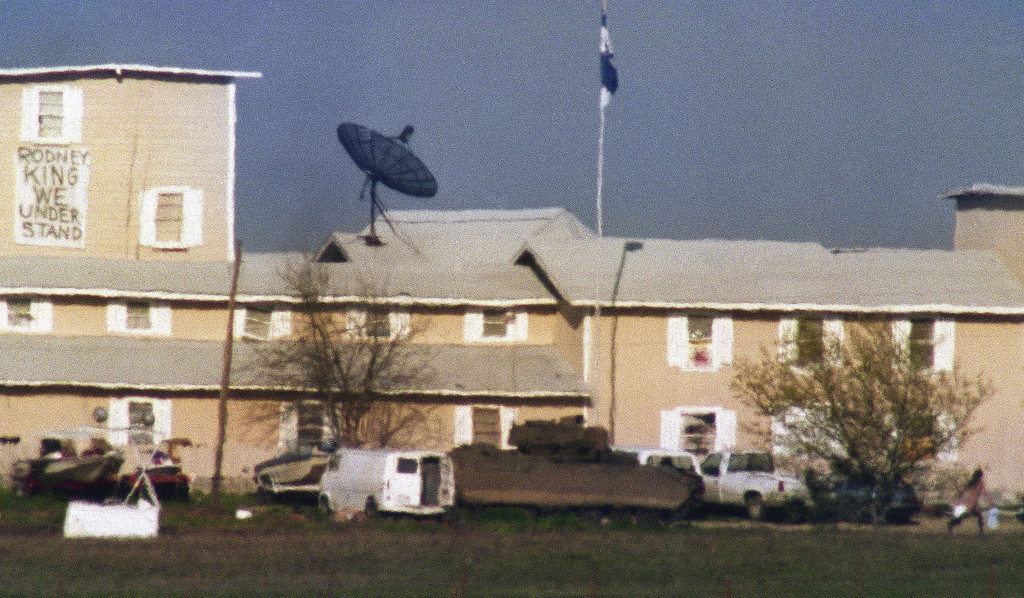 . In this March, 26, 1993 file photo, a person can be seen in the lower right hand corner of the photo running back to the Branch Davidian compound near Waco, Texas. The 20th anniversary of the botched raid on the Branch Davidians compound passed quietly Thursday, Feb. 28, 2013, as colleagues of the four agents who died gathered in private and local officials made no plans to note the day. The Bureau of Alcohol, Tobacco, Firearms and Explosives held a ceremony in Waco to honor agents Conway LeBleu, Todd McKeehan, Robert John Williams and Steven Willis, the four agents who died in the Feb. 28, 1993 raid. Six Davidian members also died in that raid, which began a 51-day standoff that ended in a fire and the deaths of about 80 more sect members, including two dozen children.  (AP Photo/Rick Bowmer, File)
