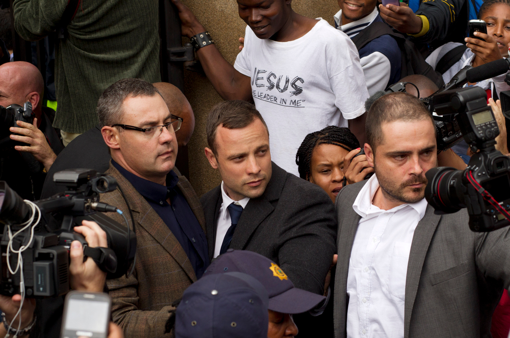 . Oscar Pistorius, center, is escorted out by police officers as he leaves  the high court on the second day of his trial in Pretoria, South Africa, Tuesday, March 4, 2014. Oscar Pistorius is charged with murder for the shooting death of his girlfriend, Reeva Steenkamp, on Valentines Day in 2013. (AP Photo/Themba Hadebe)