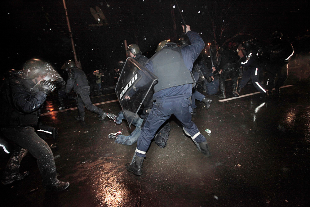 Description of . Protesters are beaten and detained by riot police during a protest against high electricity prices in Sofia, on late Tuesday, Feb. 19, 2013.  Bulgaria's prime minister announced on Tuesday that the license held by a Czech company for power distribution in parts of the Balkan country will be revoked following protests against high electricity prices. (AP Photo/Valentina Petrova)