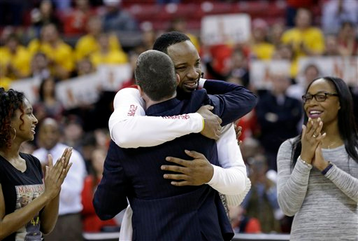 . Maryland guard/forward Dez Wells hugs head coach Mark Turgeon as family members look on during a senior day ceremony before an NCAA college basketball game against Michigan, Saturday, Feb. 28, 2015, in College Park, Md. (AP Photo/Patrick Semansky)