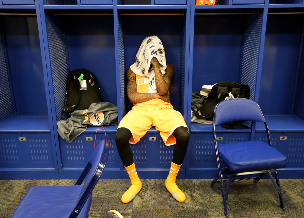 . Tennessee guard Antonio Barton (2) looks down in the locker room after an NCAA Midwest Regional semifinal college basketball tournament game Friday, March 28, 2014, in Indianapolis. Michigan won 73-71. (AP Photo/Michael Conroy)