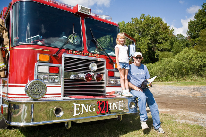 Alyssa Morgan and Tom Morgan sit on front of firetruck.