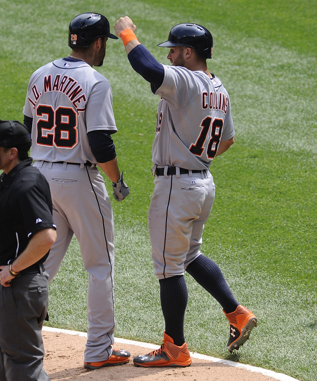 . Detroit Tigers  J.D. Martinez, left, gets high-fived by Detroit Tigers Tyler Collins after Martinez hit a two run home run during the sixth inning of baseball game against the Chicago White Sox in Chicago on Sunday, June 7,  2015. Collins also scored on the hit. (AP Photo/Matt Marton)