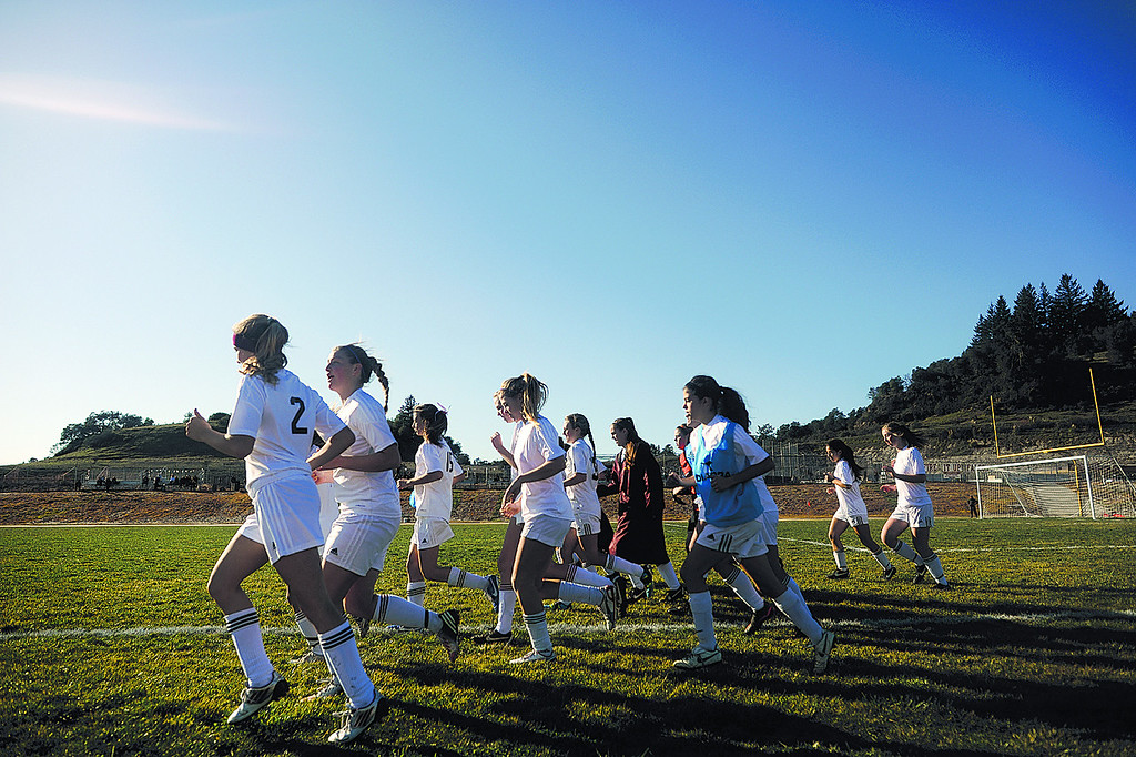 . Scotts Valley High players hustle back from their huddle to the bench before the start of the second half of their first-round Central Coast Section Division III girls soccer game on Feb. 20, 2013. The King\'s Academy won 1-0. (Matthew Hintz/Sentinel).