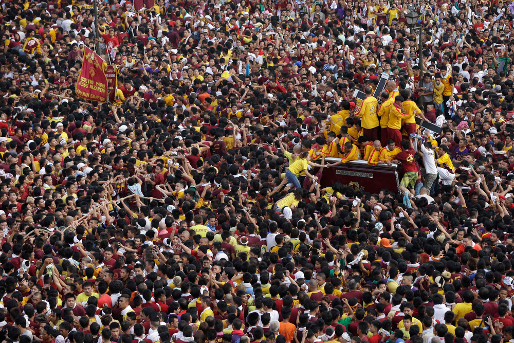 . Catholic devotees jostle to get closer to the centuries-old image of the Black Nazarene in a raucous celebration on its feast day Wednesday Jan. 9, 2013 in Manila, Philippines. The annual procession by hundreds of thousands of devotees is now becoming to be a tourist attraction.  More than a hundred devotees were treated for minor injuries. (AP Photo/Bullit Marquez)
