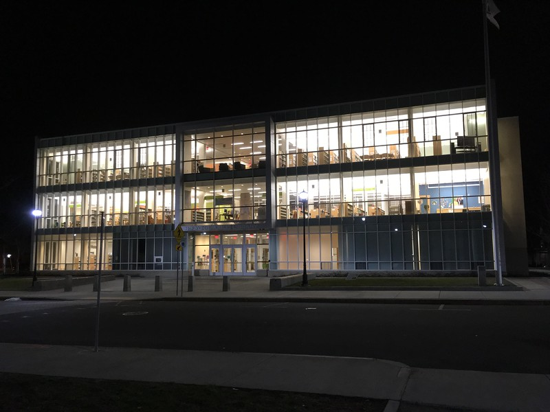 View of the Library at the close of Friday night's party. Some props for Mini Golf holes visible in the windows, e.g., wide screen TV from Aaron's in upper right, and a River Valley Counseling Center poster on Level 2, right.