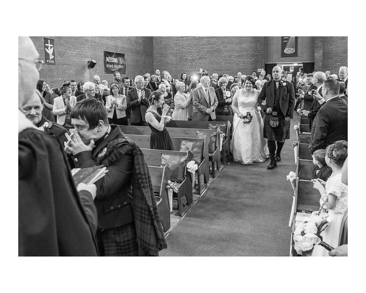 Wedding Photography of Rhona & Alan, Tron St Marys Church, Glasgow, Photograph is of the Bride being walked down the aisle and the groom crying at the end