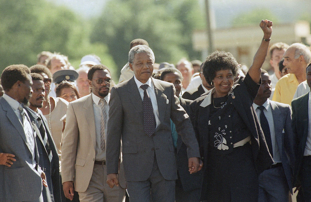 . Nelson Mandela is led by his wife, Winnie Mandela, who gives a black power salute, after his release from Victor Verster prison in Cape Town, South Africa, on Sunday, Feb. 11, 1990. The leader of the African National Congress served over 27 years in jail. (AP Photo/Greg English)