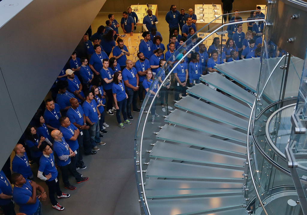 . Apple store employees wait for doors to open to customers for the first day of sale of the iPhone 6 and 6 Plus, Friday, Sept. 19, 2014,  in New York. Several hundred people lined up outside the store in Manhattan to buy the highly anticipated phones. (AP Photo/Julie Jacobson)