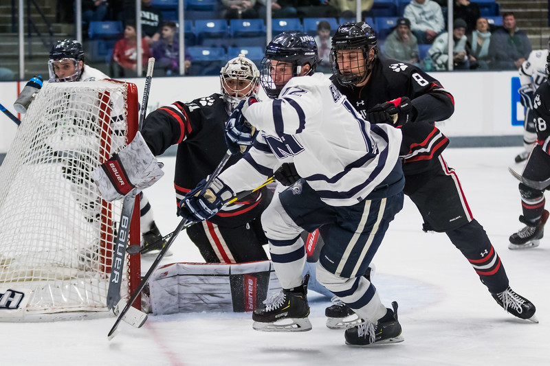 New Hampshire's Eric Esposito (12) chases the puck into the corner while being defended by Northeastern's Julian Kislin during Hockey East action in Durham Friday. [Scott Patterson/Fosters.com]