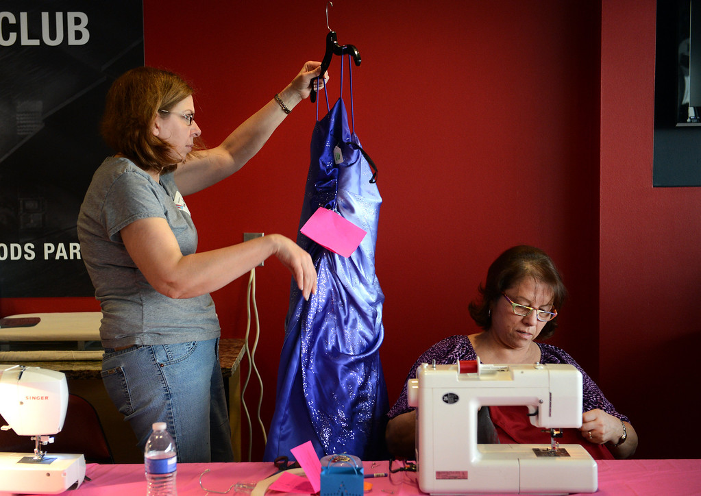 . COMMERCE CITY, CO. - MARCH 16: Volunteers Nancy Parker, left, and Gloria Maez, make alterations during the Prom Dress Exchange Corp. event in Commerce City, CO March 16, 2013.  For the third year, the organization offered teens an opportunity to find a dress for the big night. With a valid student ID and a suggested $10 donation, teenage girls could chose from 1,356 donated dresses that lined a long hallway at Dick�s Sporting Goods Park.  (Photo By Craig F. Walker/The Denver Post)