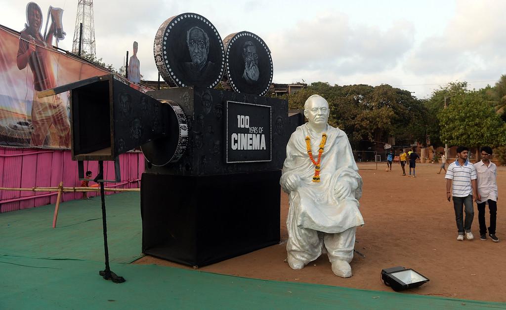 """. Patrons walk past a statue of Indian filmmaker Dadasaheb Phalke placed outside the Anup Touring Talkies tent cinema at a ground in central Mumbai on April 19, 2013.  To mark 100 years of Indian Cinema, a Marathi film \""""Touring Talkies\"""" is being screened in a makeshift tent theatre just like the days of yore, in its pre-multiplex and pre-single screen glory dating back 50 years. The tents, keeping in mind modern audiences, will have plush seating, air conditioning and popcorn and cola alongside fresh sugar-cane juice, roasted groundnuts and gram and pickle and other tit-bits. The cinema will screen four shows per day for a week. The idea of touring talkies was the brainchild of the doyne of Indian cinema, Dadasaheb Phalke, after he saw the British watching movies in tents. The touring cinema would travel through rural India and screen movies in makeshifts tents. At present, one can only find these talkies - whose sweltering tents and basic facilities contrast with the plush, air-conditioned multiplexes springing up in Indian cities, during Jatras (village fairs) in the interiors of the state.  INDRANIL MUKHERJEE/AFP/Getty Images"""