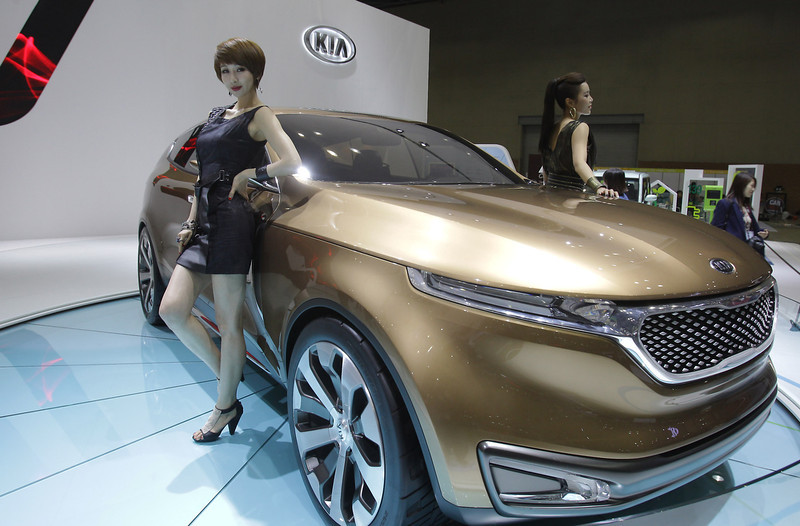 . Models pose next to a KIA Eco Hybrid at the Seoul Motor Show 2013 on March 28, 2013 in Goyang, South Korea. The Seoul Motor Show 2013 will be held in March 29-April 7, featuring state-of-the-art technologies and concept cars from global automakers. The show is its ninth since the first one was held in 1995. About 384 companies from 14 countries, including auto parts manufacturers and tire makers, will set up booths to showcase trends in their respective industries, and to promote their latest products during the show.  (Photo by Chung Sung-Jun/Getty Images)