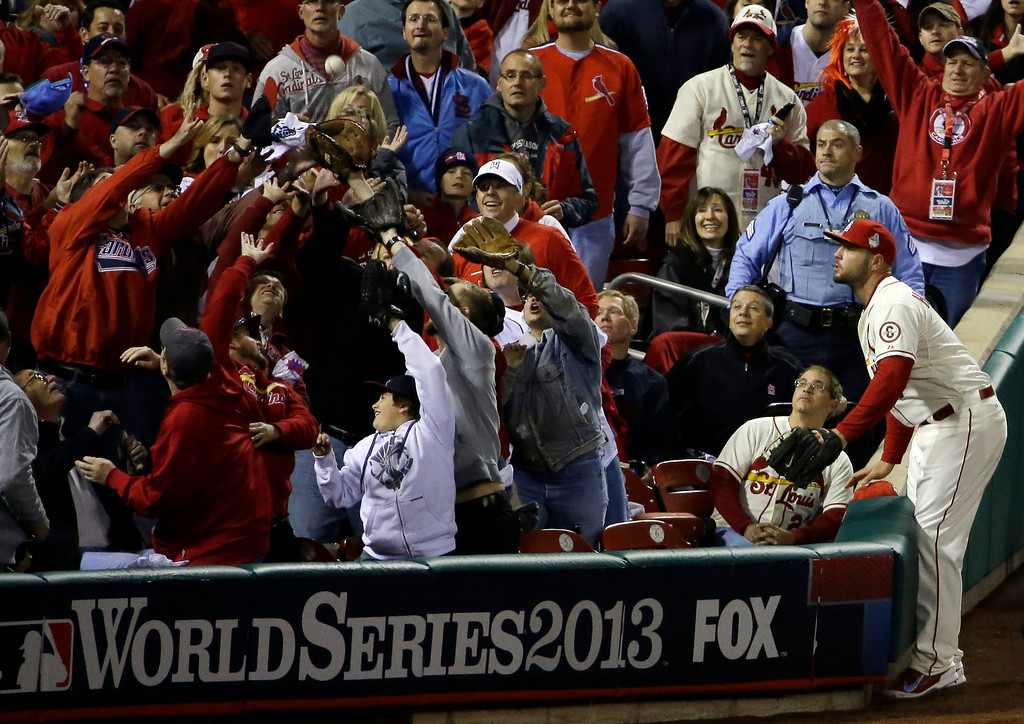 . St. Louis Cardinals\' Matt Holliday watches as fans try and catch a foul ball hit by Boston Red Sox\'s Jacoby Ellsbury during the first inning of Game 3 of baseball\'s World Series Saturday, Oct. 26, 2013, in St. Louis. (AP Photo/David J. Phillip)