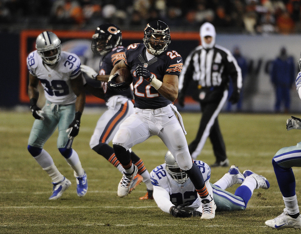 . Matt Forte #22 of the Chicago Bears runs past Jarius Wynn #92 of the Dallas Cowboys during the first quarter on December 9, 2013 at Soldier Field in Chicago, Illinois. (Photo by David Banks/Getty Images)