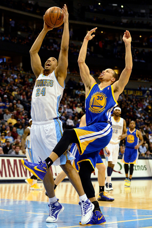 . Denver Nuggets point guard Andre Miller (24) skies for a rebound over Golden State Warriors point guard Stephen Curry (30) during the first half at the Pepsi Center on Sunday, January 13, 2013. AAron Ontiveroz, The Denver Post