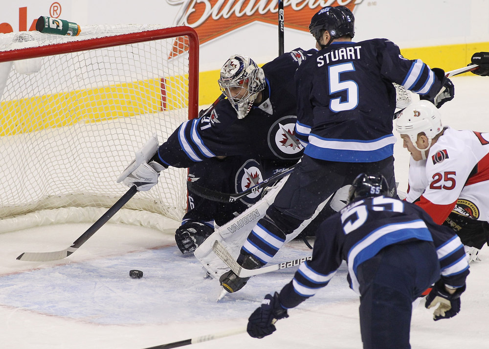 . WINNIPEG, MB - JANUARY 19:  Ondrej Pavelec #31 of the Winnipeg Jets reaches but can\'t stop Chris Neil #25 of the Ottawa Senators from scoring during second period action on January 19, 2013 at the MTS Centre in Winnipeg, Manitoba, Canada. (Photo by Marianne Helm/Getty Images)