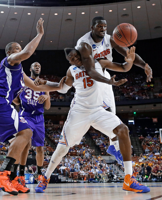 . Florida\'s Patric Young, right, reaches over teammate Will Yeguete (15) while chasing a rebound along with Northwestern State\'s DeQuan Hicks, left, during the first half of a second-round game of the NCAA men\'s college basketball tournament Friday, March 22, 2013, in Austin, Texas. (AP Photo/David J. Phillip)