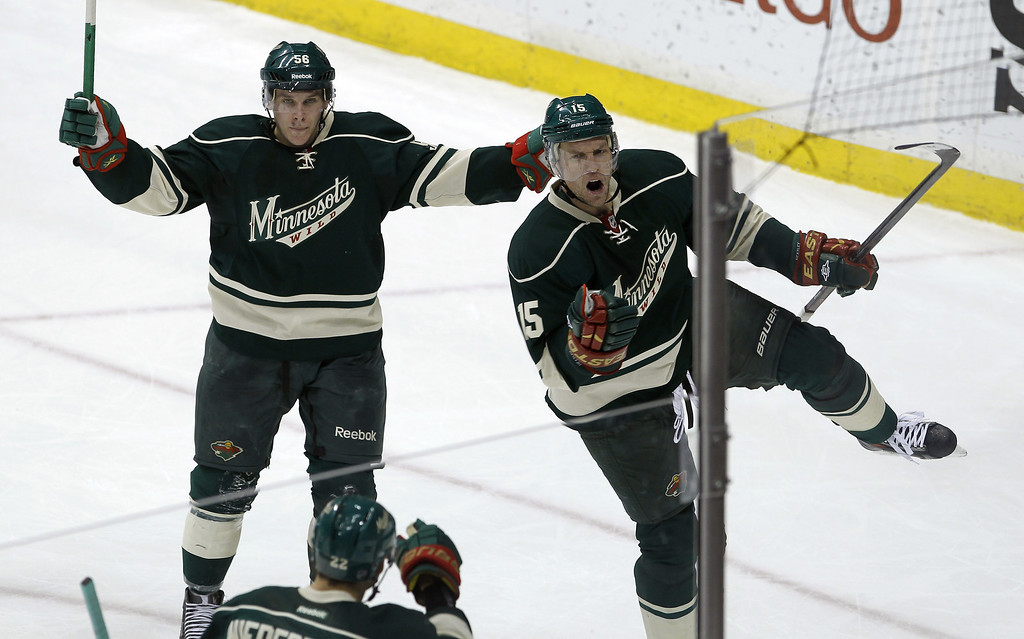 . Minnesota Wild left wing Dany Heatley, right, celebrates after scoring against Colorado Avalanche goalie Jean-Sebastien Giguere as Wild center Erik Haula, top left, joins the celebration during the second period of an NHL hockey game in St. Paul, Minn., Friday, Nov. 29, 2013. (AP Photo/Ann Heisenfelt)