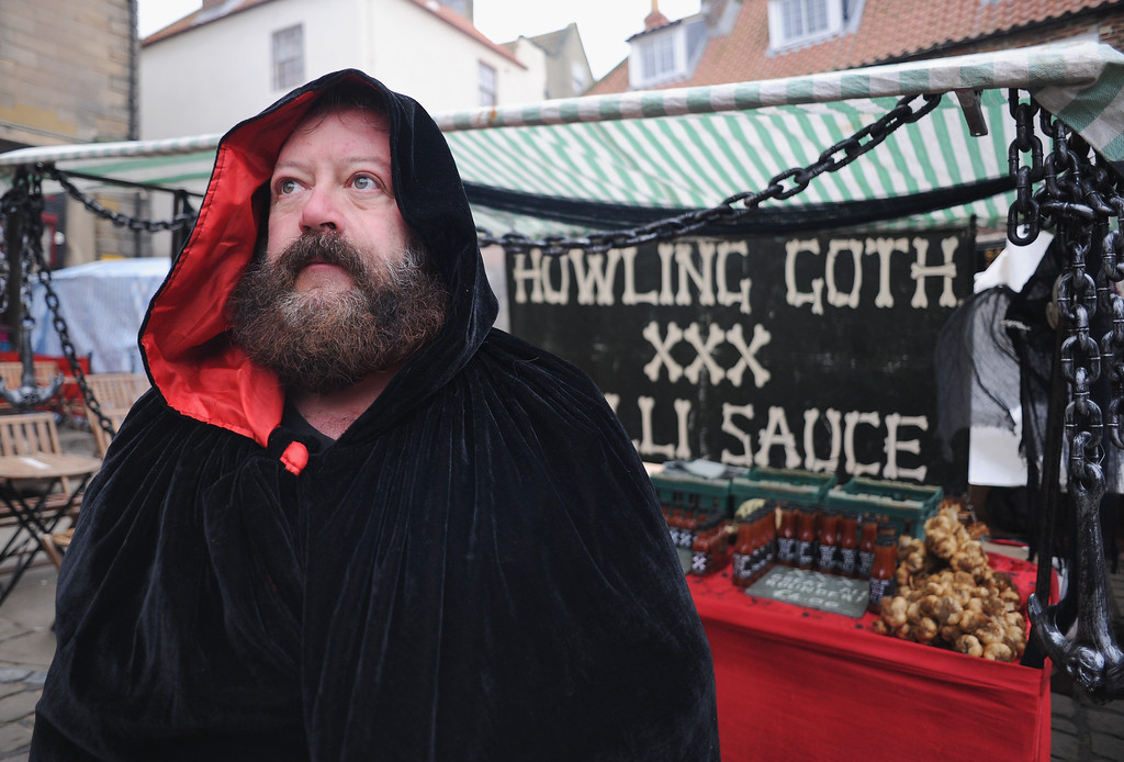 . WHITBY, ENGLAND - NOVEMBER 02: Chris Carabine from Teesside runs a stall selling Howling Goth Chilli sauces during the goth weekend on November 2, 2013 in Whitby, England. The Whitby Gothic Weekend that takes place in the Yorkshire seaside town twice yearly in Spring and Autumn started in 1994 and sees thousands of extravagantly dressed followers of Victoriana, Steampunk, Cybergoth and Romanticism visit to take part in celebrating Gothic culture.  (Photo by Ian Forsyth/Getty Images)