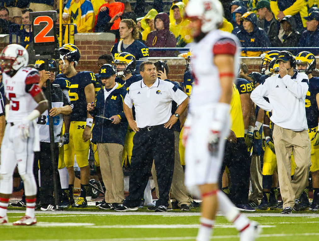 . Michigan head coach Brady Hoke, center background, stands on the sideline in the fourth quarter of an NCAA college football game against Utah in Ann Arbor, Mich., Saturday, Sept. 20, 2014. (AP Photo/Tony Ding)