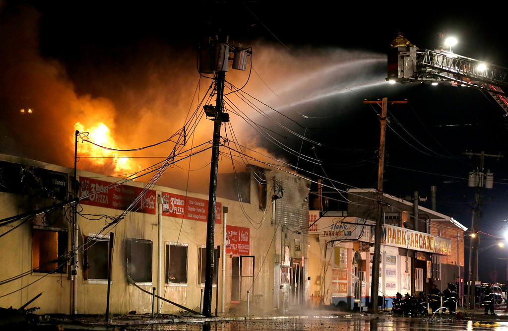 . Firefighters battle a blaze in a building on the Seaside Park boardwalk on Thursday, Sept. 12, 2013, in Seaside Park, N.J. The fire began in a frozen custard stand on the Seaside Park section of the boardwalk and quickly spread north into neighboring Seaside Heights. (AP Photo/Julio Cortez, File)