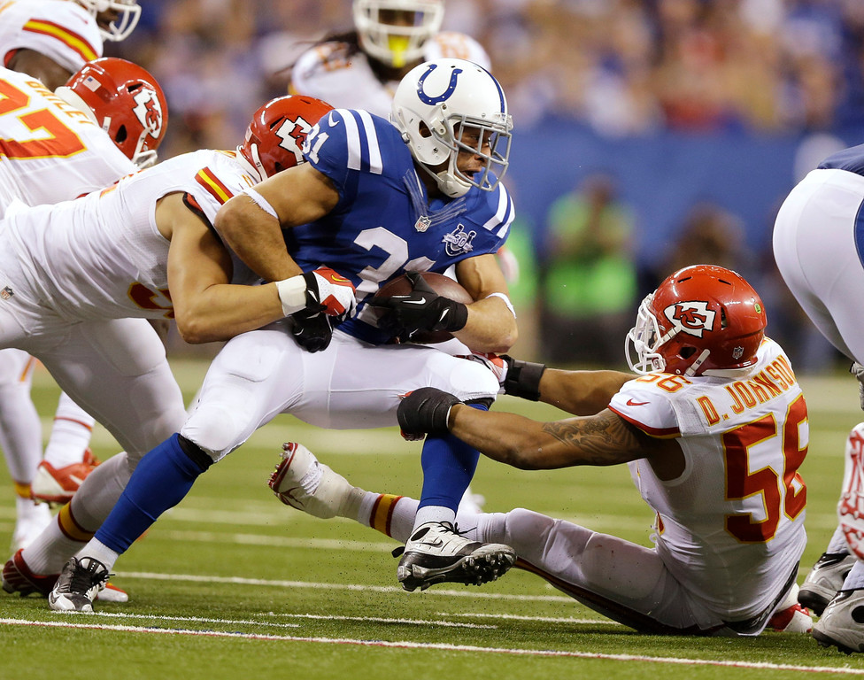 . Indianapolis Colts\' Donald Brown (31) is tackled buy Kansas City Chiefs\' Derrick Johnson (56) during the second half of an NFL wild-card playoff football game Saturday, Jan. 4, 2014, in Indianapolis. (AP Photo/Michael Conroy)