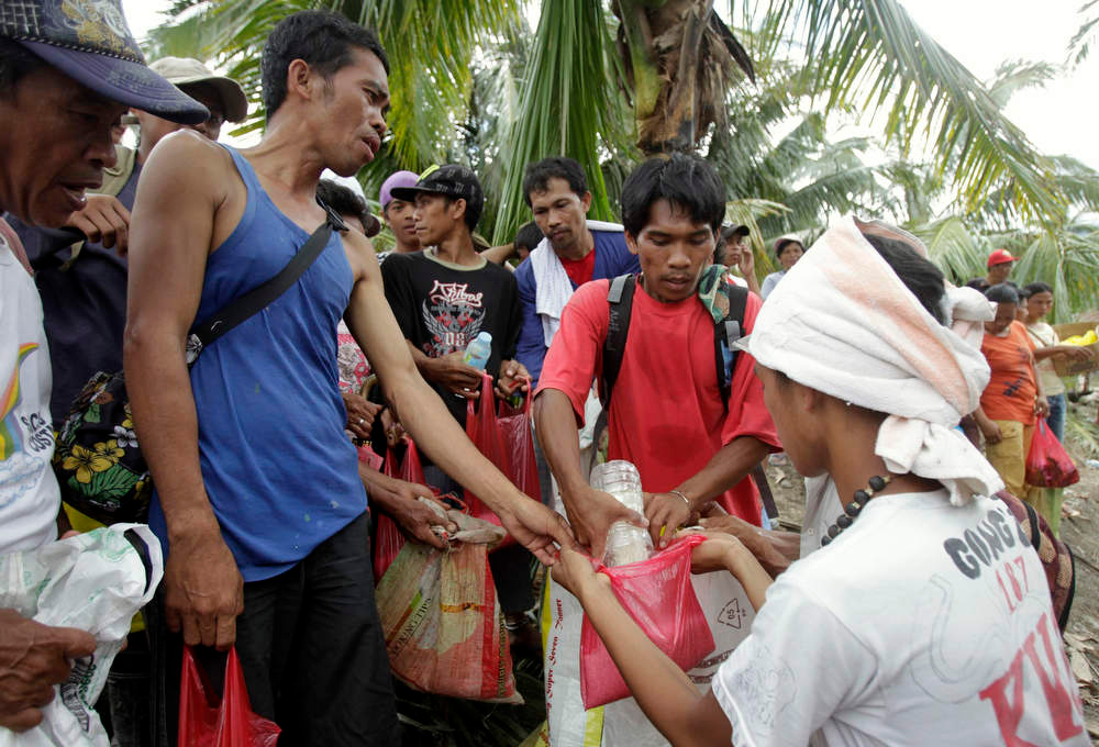 . Typhoon Bopha victims receive free rice in Andap village, in New Bataan town in Compostela Valley, southern Philippines December 8, 2012. Philippine President Benigno Aquino declared a state of national calamity on Saturday, four days after this year\'s strongest typhoon left nearly 1,000 people dead or missing mostly in the country\'s resource-rich south. REUTERS/Erik De Castro
