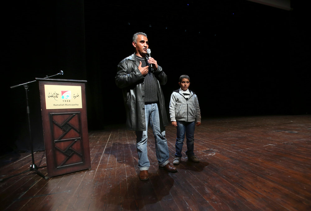 ". Palestinian journalist Emad Burnat (L) stands next to his son Jibril as he speaks to the audience after a screening of his Oscar-nominated documentary ""5 Broken Cameras\"" in the West Bank city of Ramallah January 28, 2013. The documentary screened for Palestinians for the first time on Monday, leaving locals hopeful that their struggle with Israel for land and statehood will gain a global audience. The low-cost film is based on five years of amateur camera work by Burnat as he documented weekly protests against land seizures by Israeli forces and Jewish settlers in his village of Bil\'in in the occupied West Bank. Picture taken January 28, 2013. REUTERS/Mohamad Torokman"