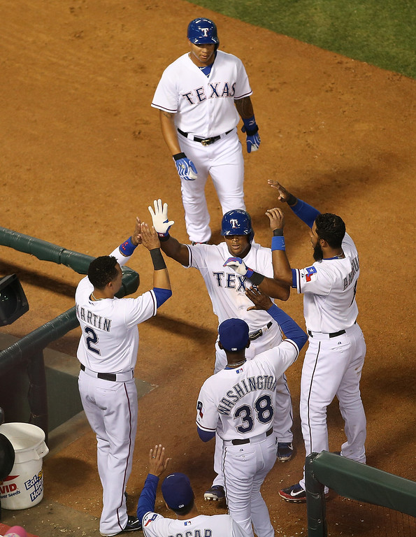 . Michael Choice #15 follows Adrian Beltre #29 of the Texas Rangers as he\'s congratulated by Leonys Martin #2, manager Ron Washington #38 and Elvis Andrus #1 for hitting a two run home run against the Colorado Rockies at Globe Life Park in Arlington on May 7, 2014 in Arlington, Texas.  (Photo by Rick Yeatts/Getty Images)