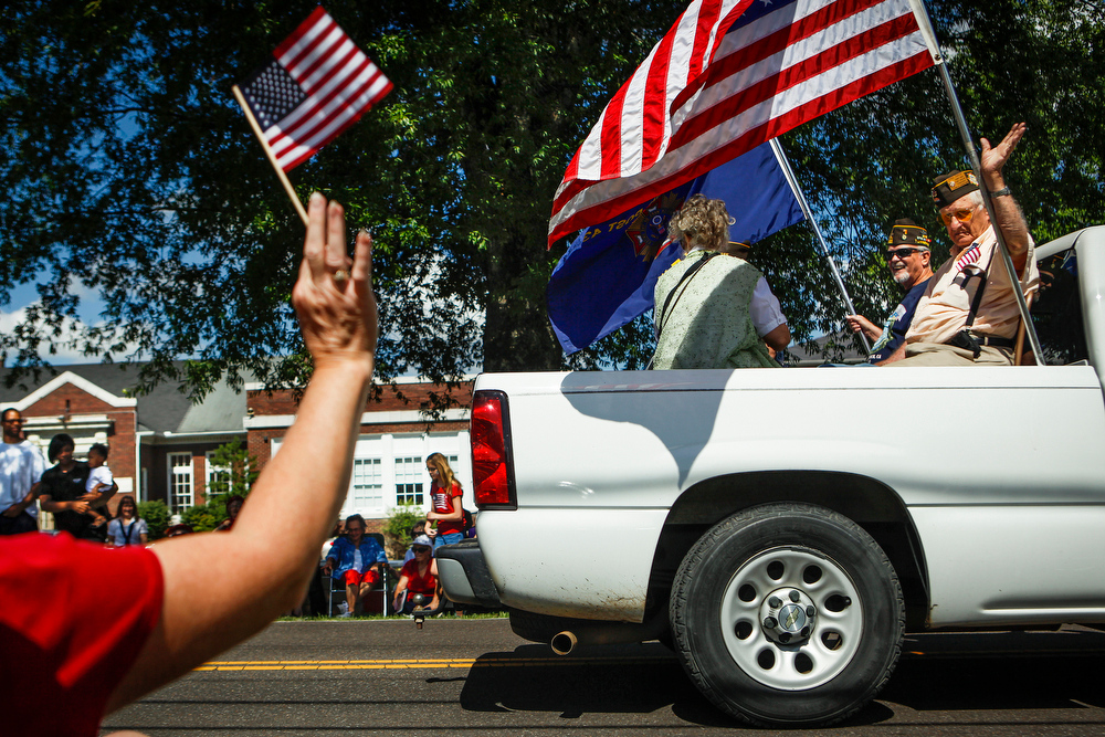 . A truck carrying members of the Veterans of Foreign Wars Post 4313 drives down the parade route during the Cordova Community Center\'s Independence Day celebration and parade in Cordova, Tenn. Friday, July 4, 2014. (AP Photo/The Commercial Appeal, William DeShazer)