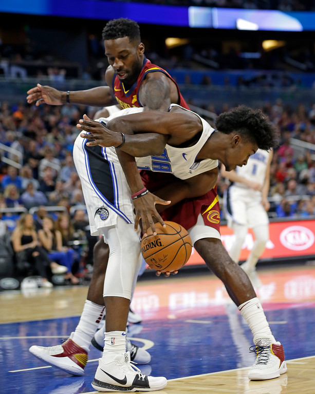 . Orlando Magic\'s Jonathan Isaac, front, gets tanged up with Cleveland Cavaliers\' Jeff Green as he grabs a rebound during the first half of an NBA preseason basketball game, Friday, Oct. 13, 2017, in Orlando, Fla. (AP Photo/John Raoux)